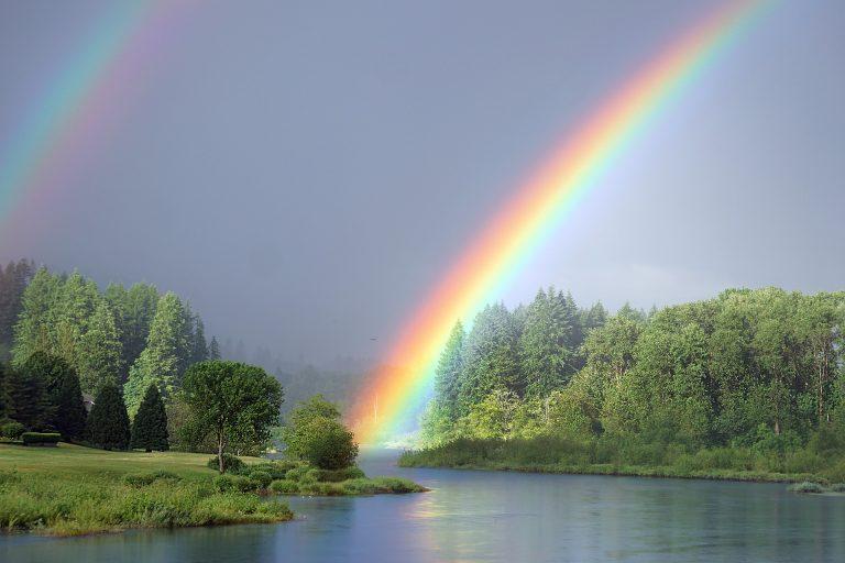 Sateenkaari vehreässä luonnonmaisemassa vesistön yllä